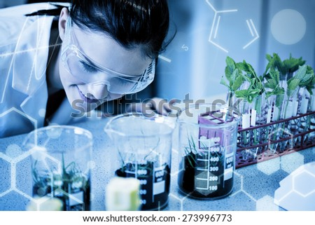 Science graphic against female researcher looking at young plants at lab - stock photo