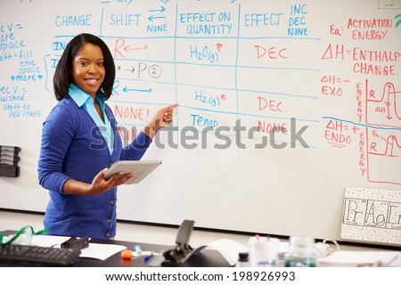 Science Teacher Standing At Whiteboard With Digital Tablet - stock photo