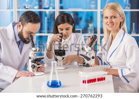 Science team working with microscopes in a laboratory. Female science looking at camera. - stock photo