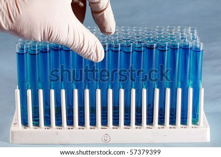 scientific and medical test tubes being held and examined by a technician wearing a rubber glove - stock photo