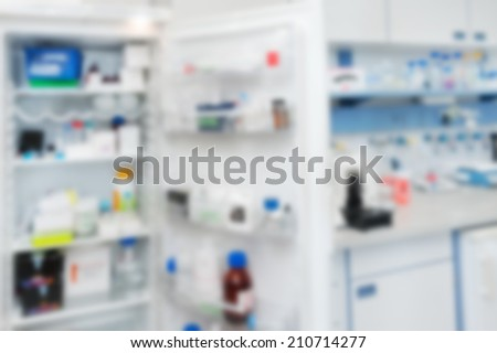 Scientific background: open fridge with reagents and laboratory interior out of focus - stock photo