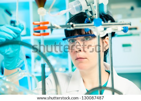 Scientific researcher holding at a liquid solution in a lab - stock photo
