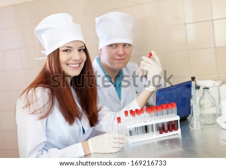 scientific workers with test tubes in laboratory - stock photo