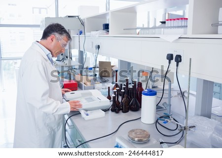 Scientist carrying out an experiment in laboratory - stock photo