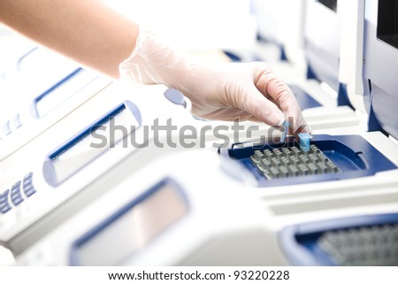 Scientist, DNA copying, Real-time PCR cycler, white gloves, distant - stock photo