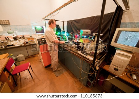 Scientist engaged in research in his lab about movement of microparticles by laser - stock photo