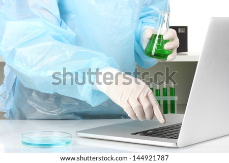Scientist entering data on laptop computer with test tube close up - stock photo