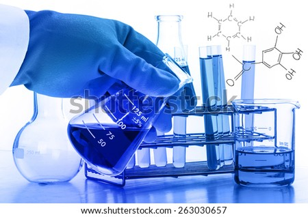 scientist hand holding laboratory test tubes - stock photo