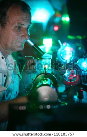 Scientist hold glasses in hand and engaged in research in his lab show movement of microparticles by laser - stock photo