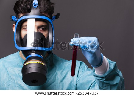 Scientist holding a sample of blood on grey background - stock photo