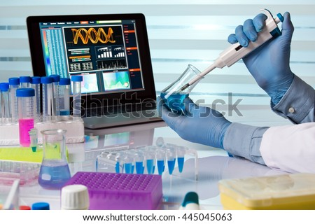 scientist holding flask and working with laptop in lab / chemical engineer working in laboratory with pipette and flask - stock photo