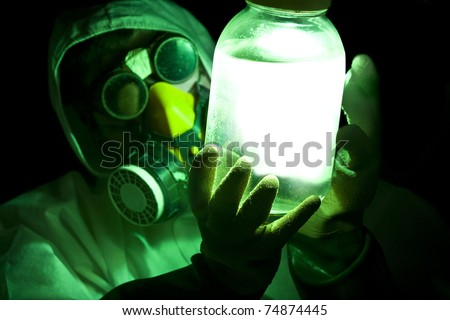 scientist holding glowing toxic substance - stock photo
