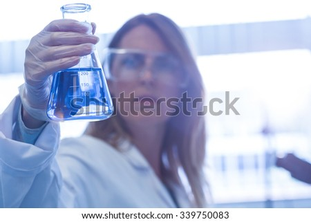 Scientist holding up beaker of chemical at the university - stock photo