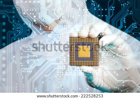 scientist in jumpsuit holding microchip and electronics circuit glow - stock photo