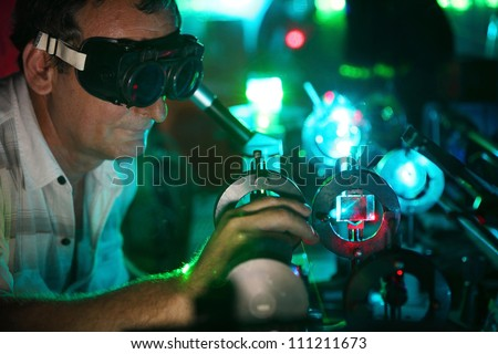 Scientist  in laser vision glasses engaged in research in his lab show movement of microparticles by laser - stock photo