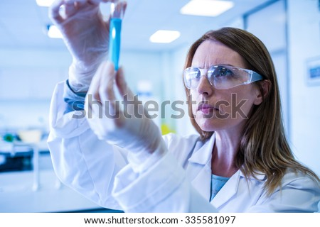 Scientist looking at test tube in the laboratory at the university - stock photo