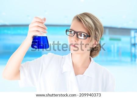 Scientist or student examining blue liquid in vial during scientific chemistry experiment - stock photo