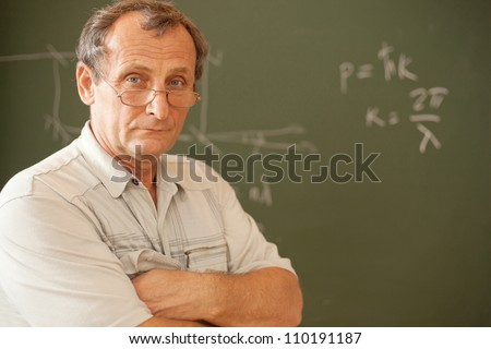 Scientist pose on background of blackboard - stock photo