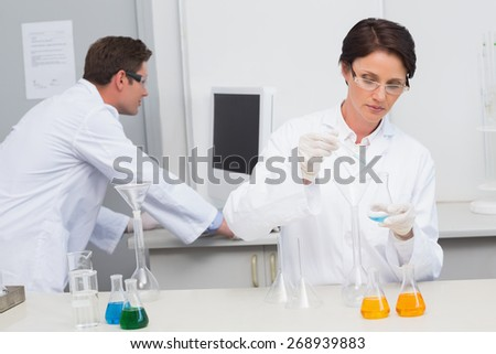 Scientist pouring chemical fluid in funnel and her colleague working with computer in laboratory - stock photo