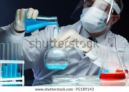 Scientist pouring fluid substances from one beaker into another - stock photo