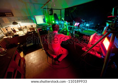 Scientist seat on chair and research in his lab about movement of microparticles by laser - stock photo