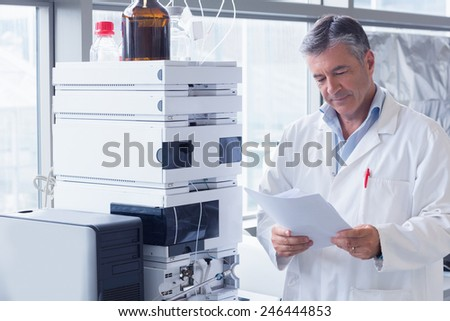 Scientist standing in lab coat reading analysis in laboratory - stock photo