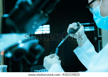 Scientist taking aliquote of an enzyme in modern lab,Young scientist works in modern biological lab,science concept,science people and selective focus. - stock photo