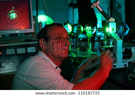 Scientist with glass demonstrate laser of microparticles in red lighting lab - stock photo