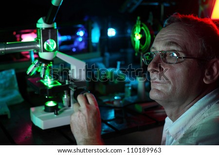 Scientist with glass demonstrate laser of microparticles, side - stock photo