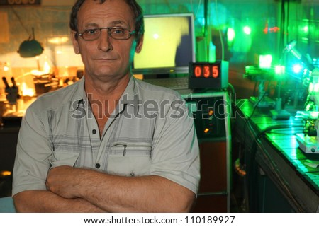 Scientist with glass pose in his lab of movement of microparticles by laser - stock photo