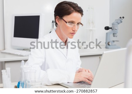 Scientist working attentively with laptop in laboratory - stock photo