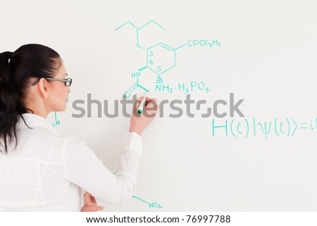 Scientist writing a formula on a white board - stock photo