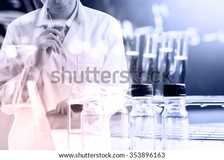 scientist writing report with equipment and science experiments, science research - stock photo