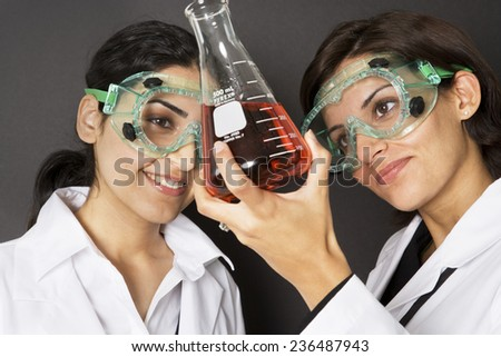 Scientists Examining Fluid in Flask - stock photo