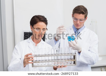 Scientists looking attentively at test tubes in laboratory - stock photo
