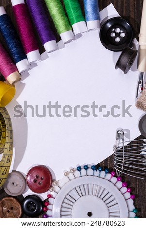 Scissors, bobbins with thread and needles on the old wooden background. Vintage Background - stock photo