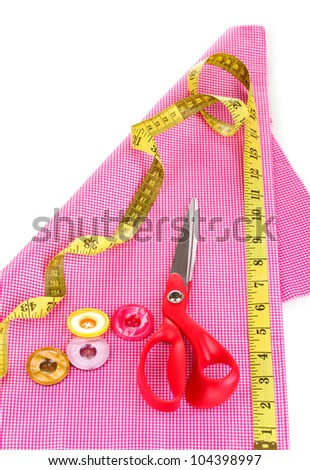 Scissors, buttons, measuring tape and pattern on fabric isolated on white - stock photo