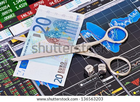Scissors cutting  euro  banknote, dices cubes with the words SELL BUY. Financial charts and columns of prices as background. Selective focus - stock photo