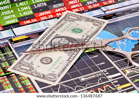 Scissors cutting  one-dollar  banknote.Financial charts and columns of prices as background. Selective focus - stock photo