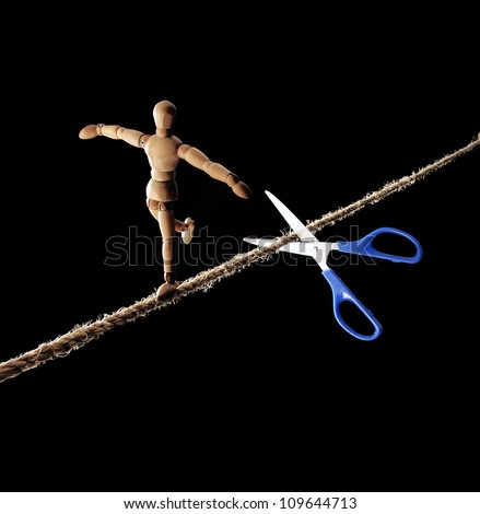 scissors cutting the rope to a tightrope walker. - stock photo
