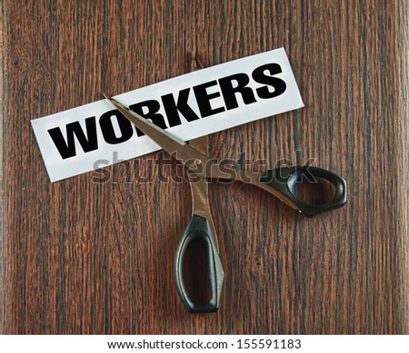 Scissors cutting the word workers written on a paper strip, over wooden background - stock photo