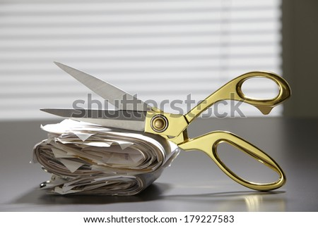 scissors resting on stack of the receipt - stock photo