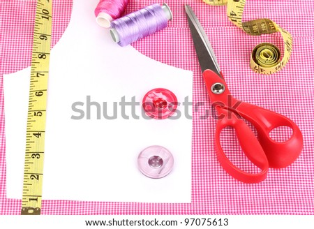 Scissors, threads, buttons, measuring tape and pattern on fabric close-up - stock photo