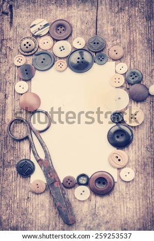 Scissors, various buttons as a border frame for the copy space around white paper. Old sewing tools on the old wooden background. Vintage Background - stock photo