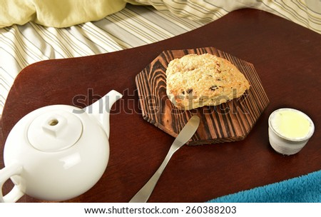 Scone on wood tray with clotted cream & tea pot on bed with sheets, pillow & blanket - stock photo