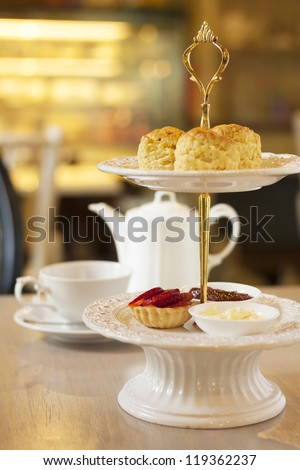 scones on two tiered tray with teapot and cup background. - stock photo