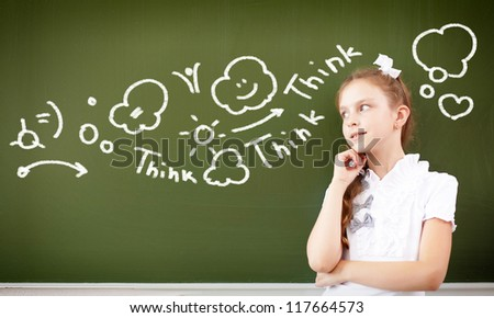 Scoolgirl standing in class near a green blackboard - stock photo