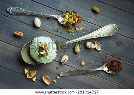 Scoop of homemade pistachio ice cream with chopped pistachios and chocolate on old wooden background. Top view. - stock photo