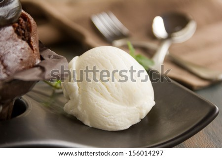 Scoop of vanilla ice cream with a chocolate muffin ready to serve. - stock photo