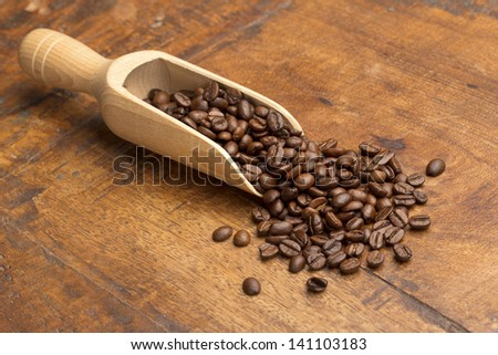 scoop with coffee beans on wooden table - stock photo